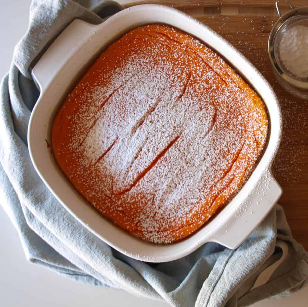 An easter dinner side Carrot Souffle Topped With Powdered Sugar on top of a wooden cutting board. A blue dish towel and powdered sugar sits next to the souffle.
