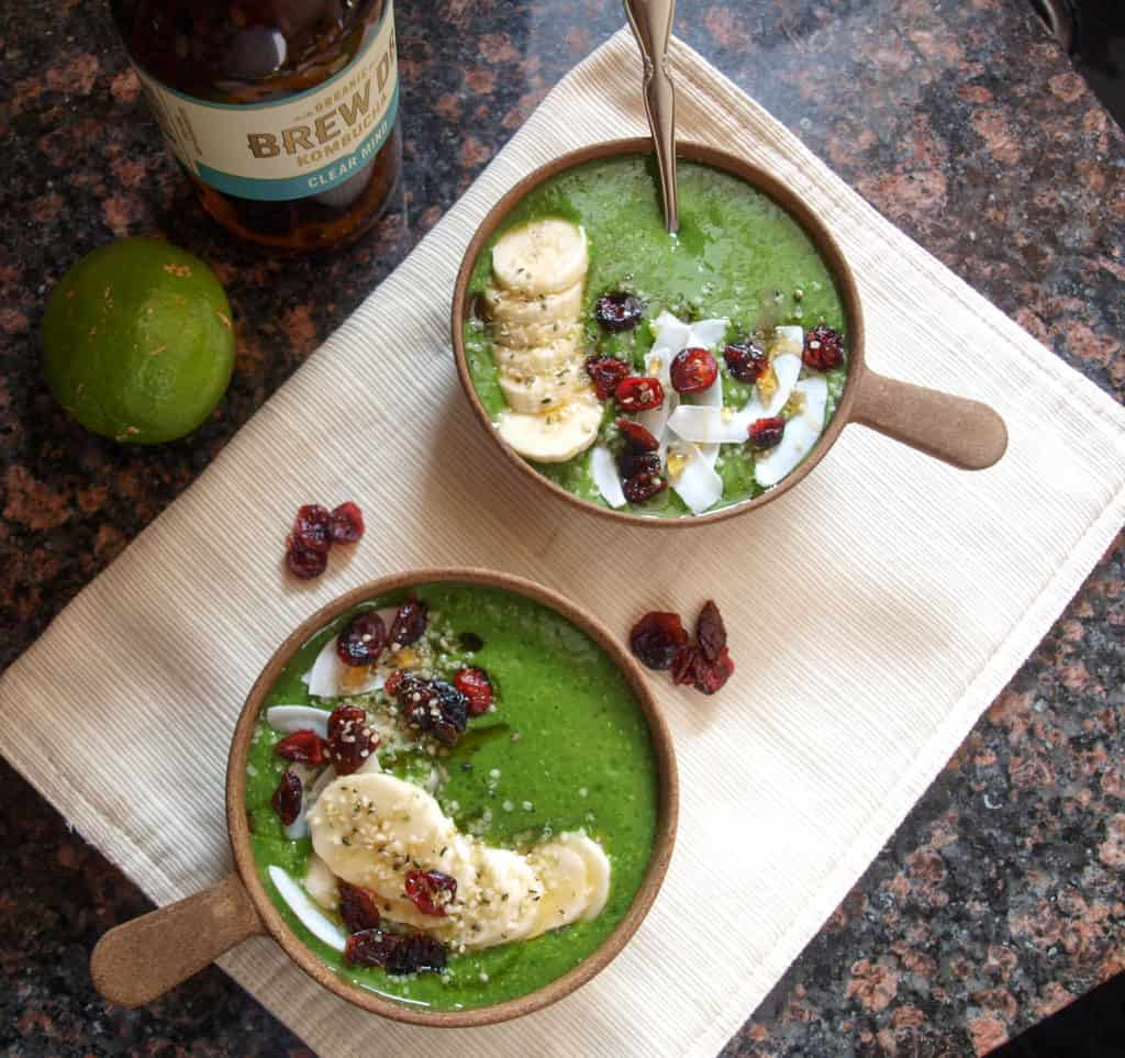 Two small bowls of Mae's Mean Green Vegan Smoothie topped with dried fruit, bananas, and hemp seeds.