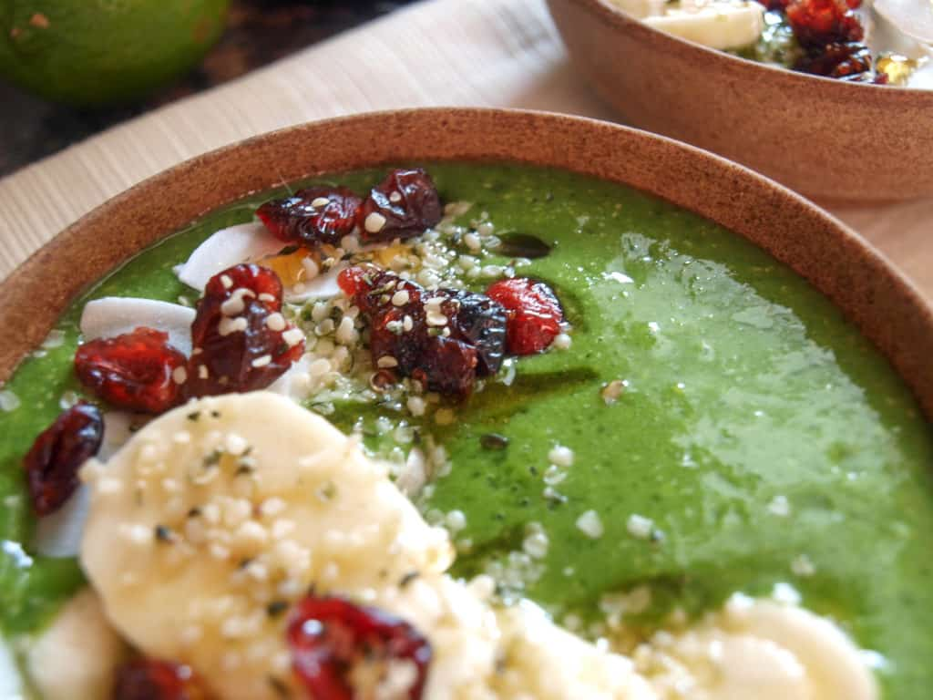 2 vegan green smoothie bowls topped with bananas, dried fruit, hemp seeds, and honey.