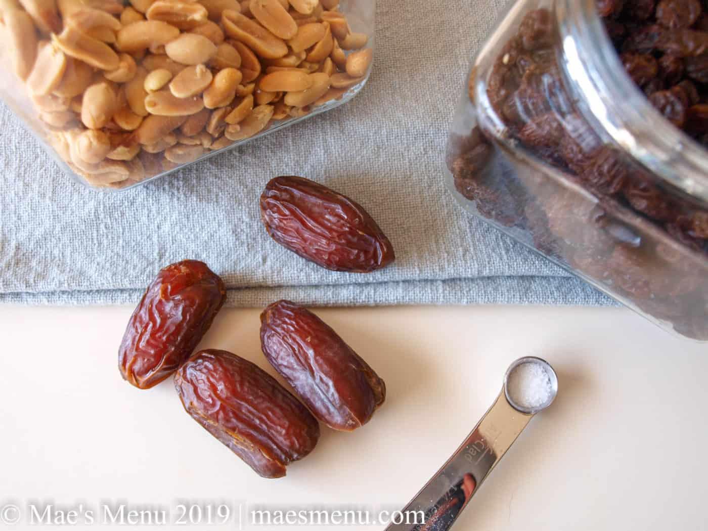 Clear glass jars of peanuts, raisins, dates, and salt.