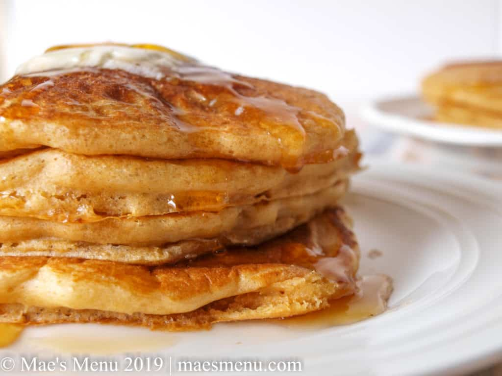 Two stacks of whole wheat pancakes with butter and syrup on top.