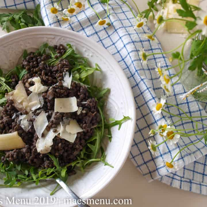 White porcelain bowl of arugula with black lentil salad and shaved hard cheese on top. Blue and white checkered towel and white and golden flowers next to the bowl.
