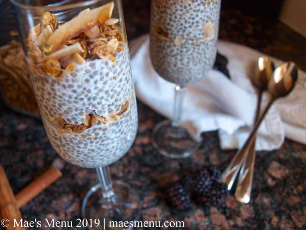 2 champagne flutes of vegan chia parfait and a glass container of granola. Blackberries, cinnamon sticks, long handled spoons, and a white dish cloth also sitting on the black granite counter.