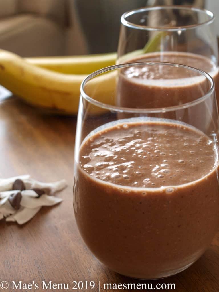 Two cups of chocolate banana smoothies with dried coconuts, chocolate chips between the cups and 2 bananas in the background.