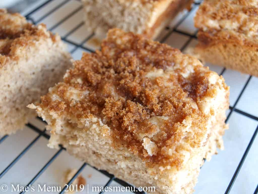 Pieces of coffee cake on a black cooling rack sitting on a white countertop.