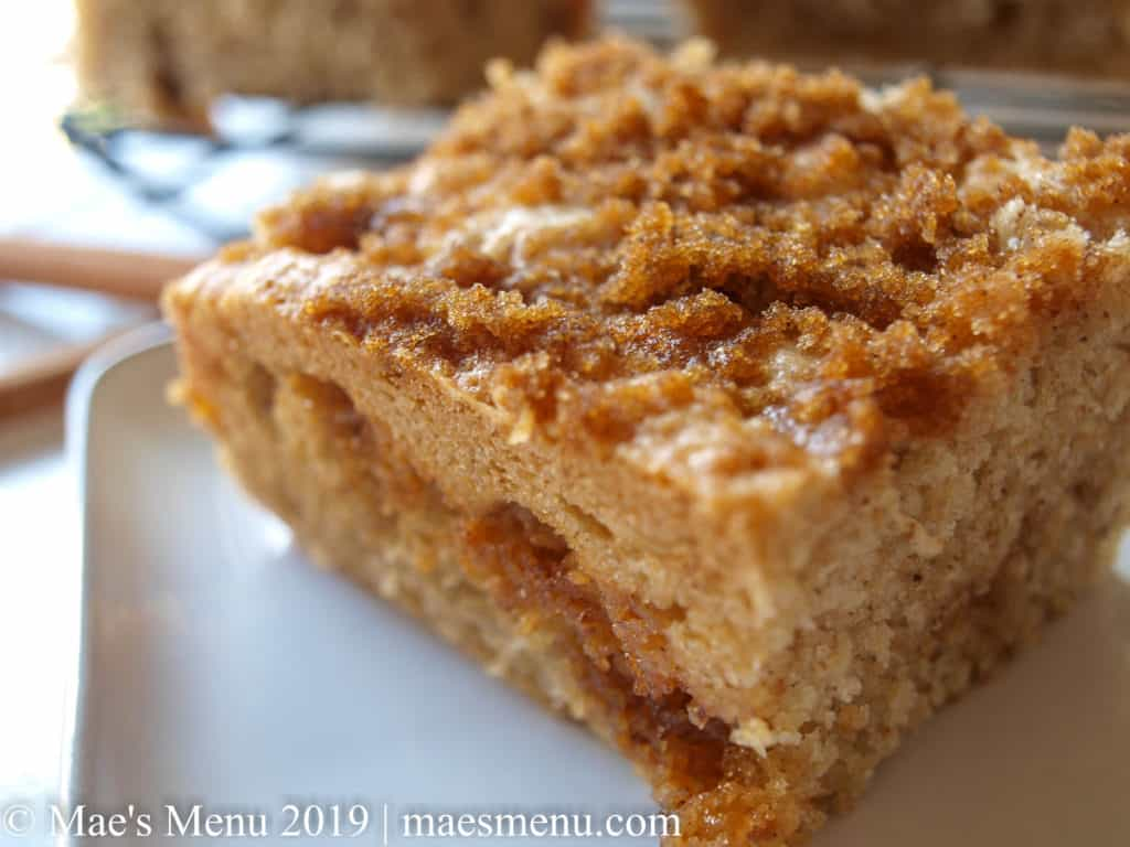 A piece of coffee cake on a white dish in front of a cooling rack of coffee cake.