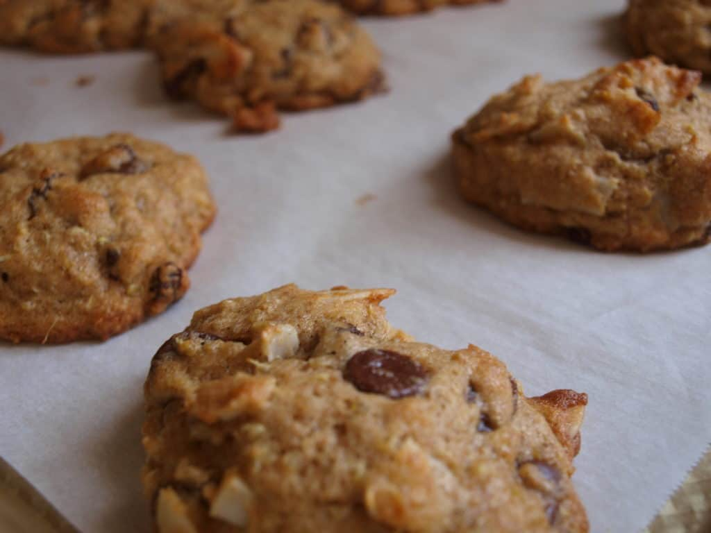 Coconut Quinoa Chocolate Chip Cookies on a parchment paper lined gold baking sheet.