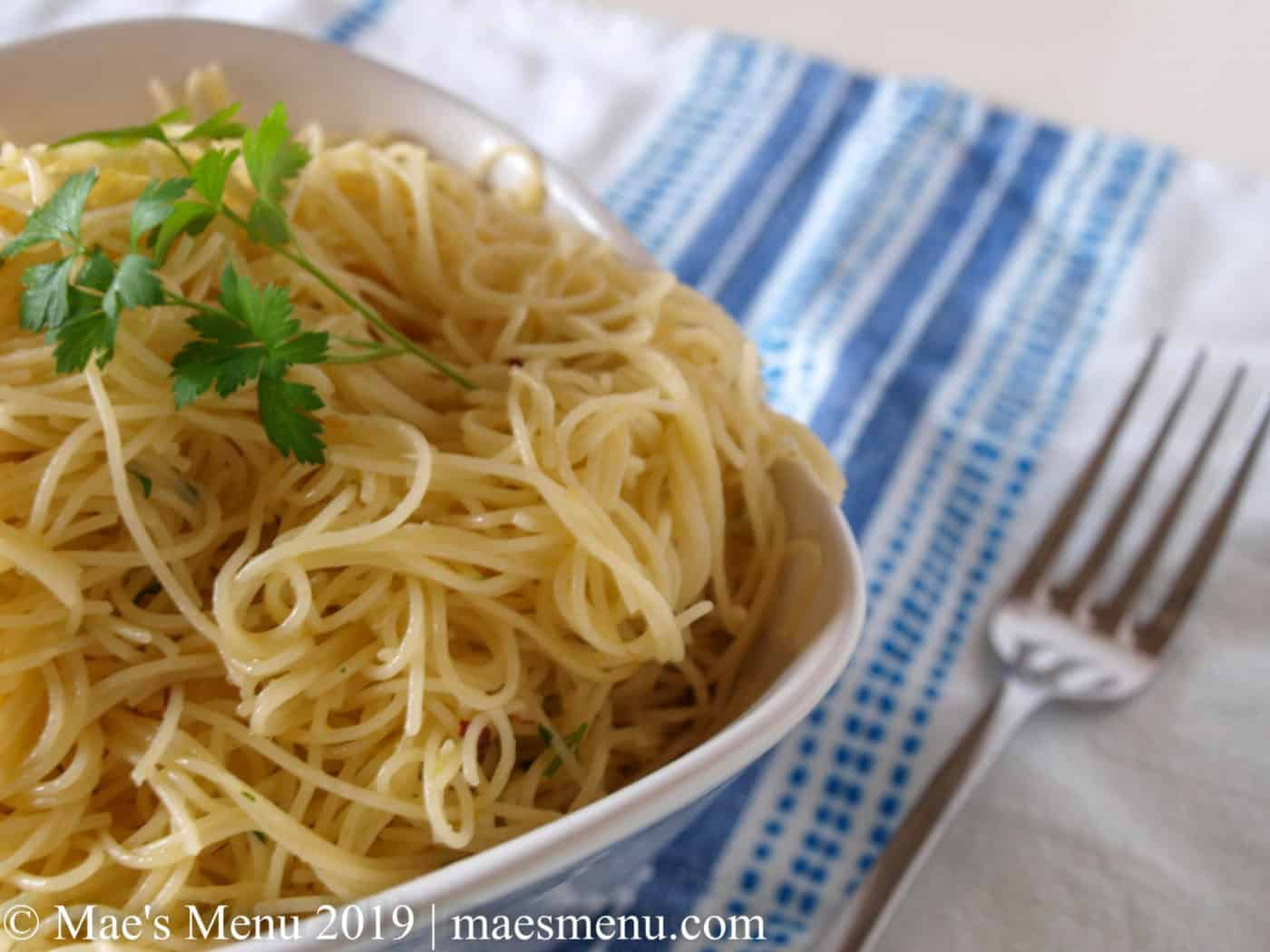 White bowl of garlic angel hair pasta and a metal fork sitting on a white dish towel with blue stripes.