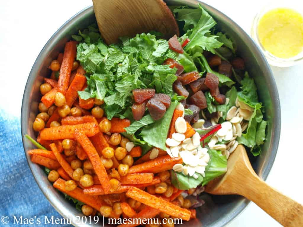 Metal bowl of baby salad greens with mint, roasted chickpeas and carrots, dried apricots, and slivered almonds on top. Salad tongs sit in the bowl with the salad and jar of preserved lemon vinaigrette sits next to bowl. Blue dish towel is on the white counter next to the bowl.