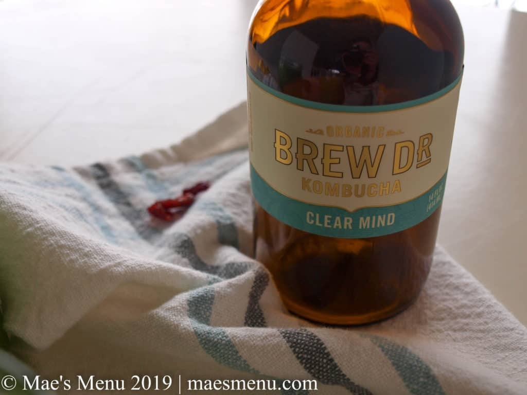 """Bottle of Brew Dr. Kombucha """"Clear Mind"""" flavor next to some cranberries on a blue striped white dish towel on a white table."""