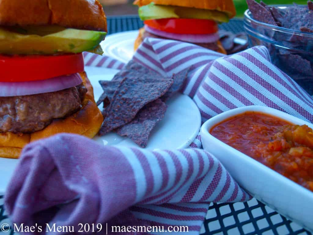 Juicy hamburgers sitting on white plates next to a purple dish towel and bowl of blue corn tortilla chips.