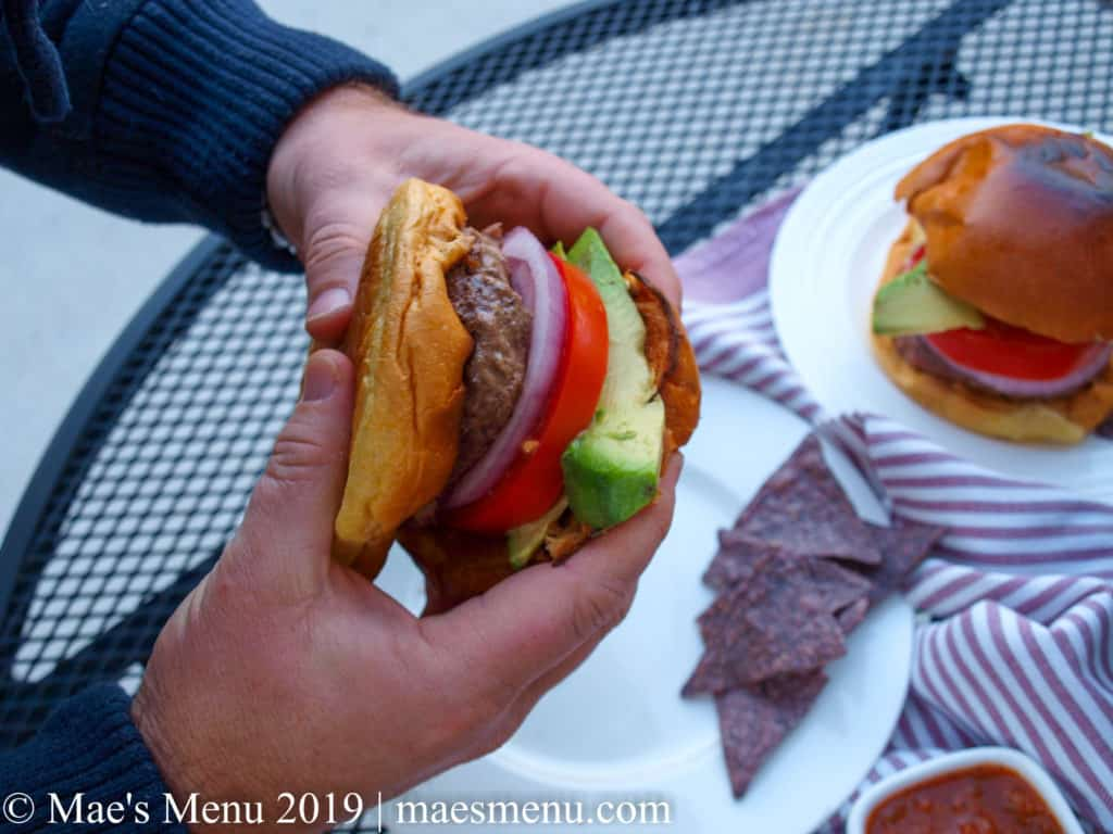 Male hands holding a burger over a table with a white plate, blue corn tortilla chips, salsa, a purple striped dish towel, and another burger on it.
