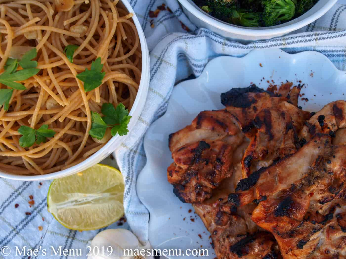 Sesame grilled chicken, garlic, half a lime, a bowl of pasta and parsley and a bowl of roasted broccoli on a white striped towel.