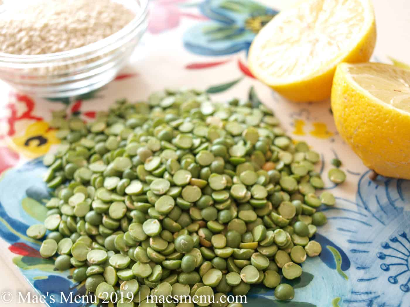 Dried split green peas, 1 lemon cut it half, and a small dish of sesame seeds on a flowered cutting board.