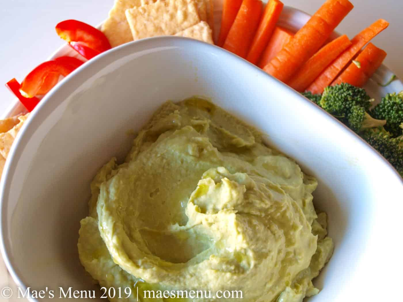 White bowl of split pea hummus surrounded by chopped veggies on a white table.