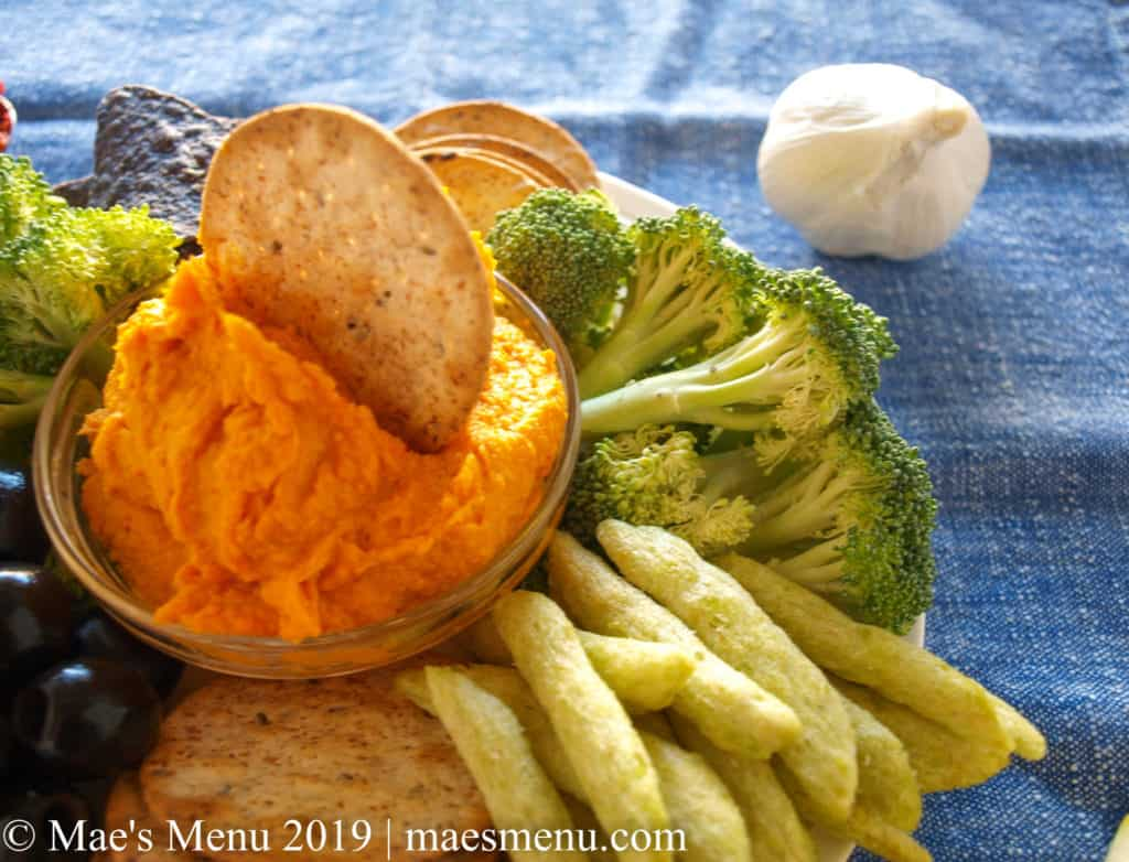 A plate of sweet potato harissa hummus, broccoli, crackers, chips, olive, and pea crisps sits on a blue dish towel next to a head of garlic.