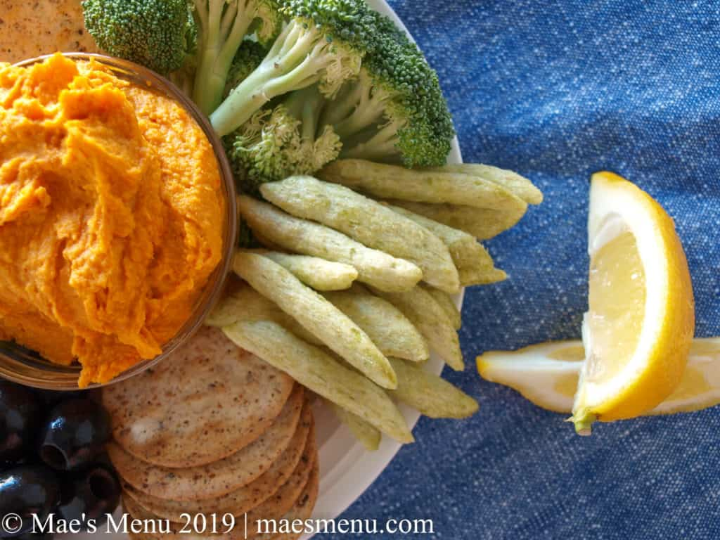 Plate of veggies and crackers and sweet potato harissa hummus on a blue dish towel.