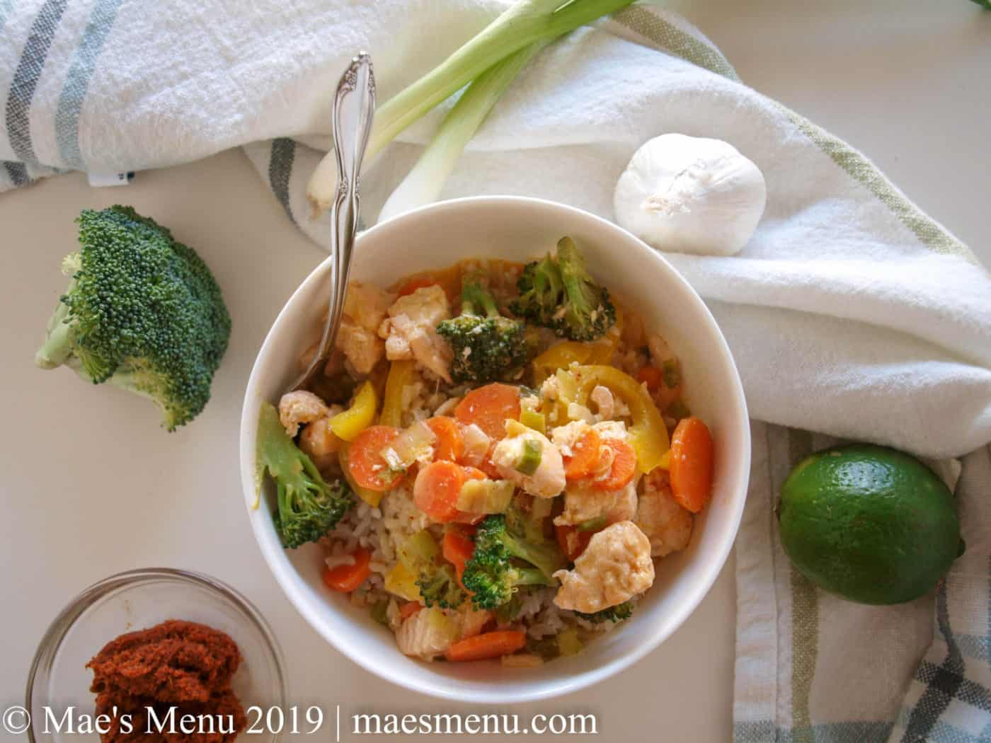 White bowl of Thai Salmon Panang Curry next to broccoli, curry paste, lime, garlic, and green onions and a white dish towel.