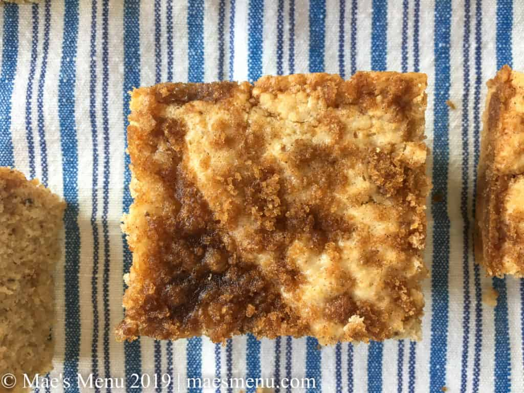 3 pieces of coffee cake on a blue striped dish towel.