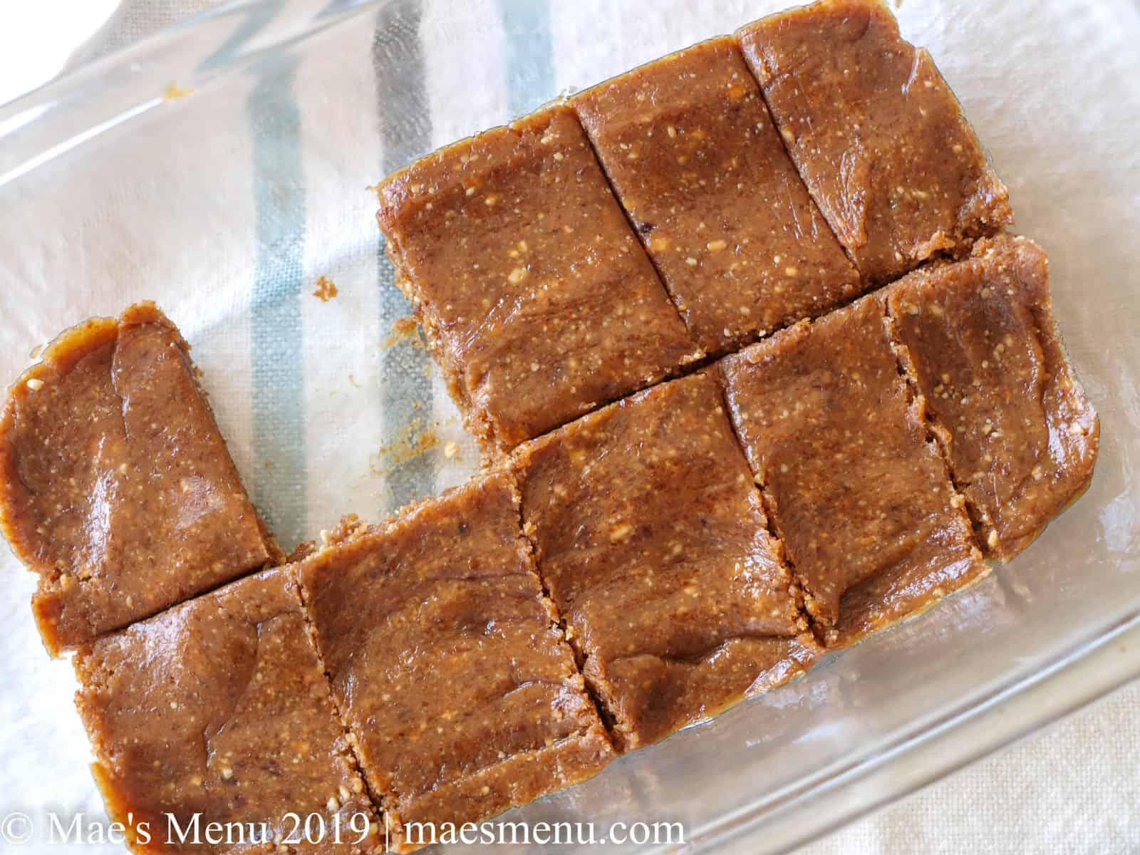 Clear glass pan of a Peanut Butter & Larabar recipe cut into pieces.