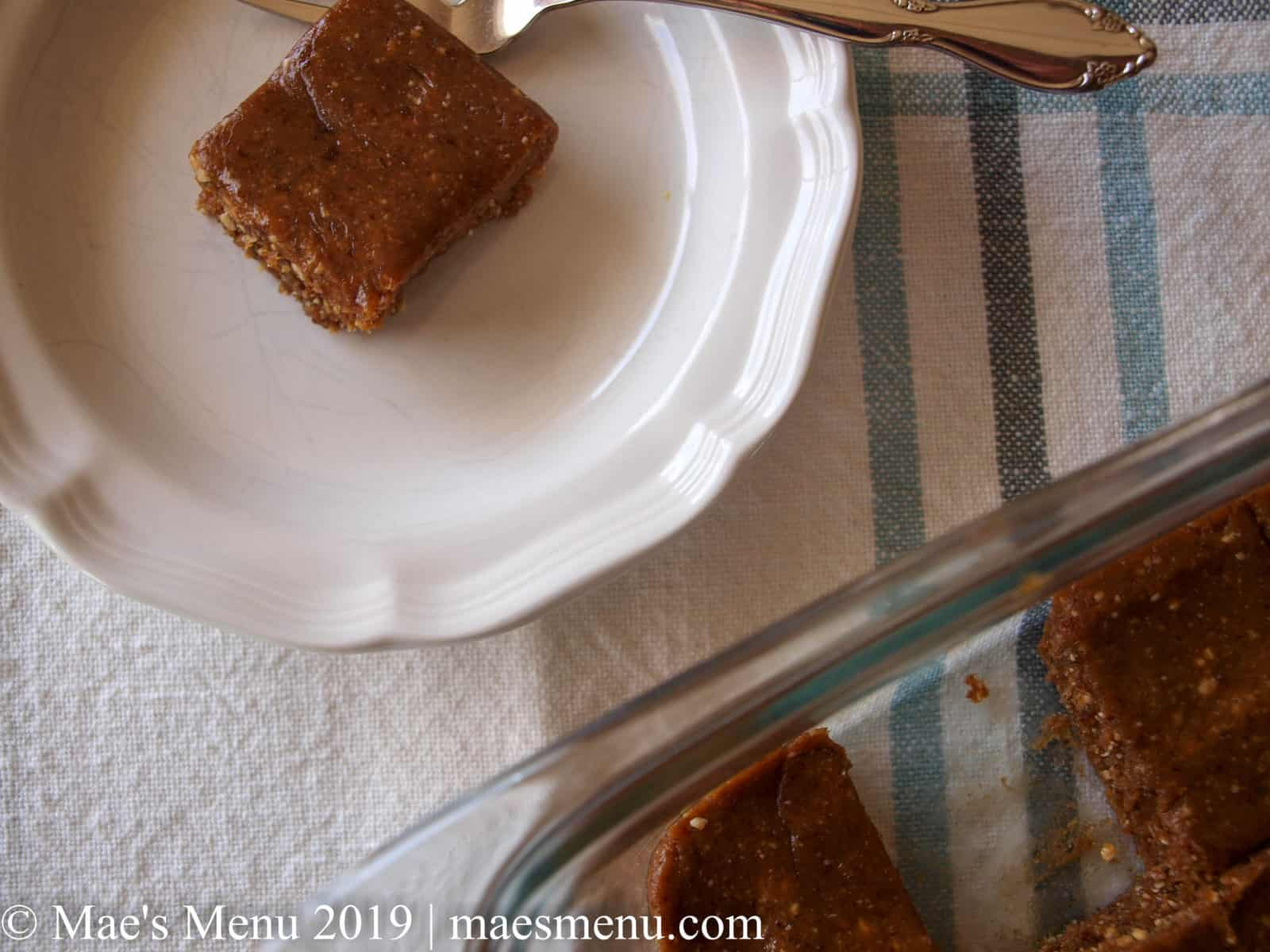 Peanut butter & Jelly larabars recipe cut into small squares and 1 square on a white small dish.