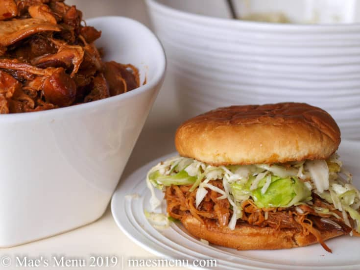 Honey BBQ shredded chicken sandwich on a white plate next to a bowl of bbq chicken.