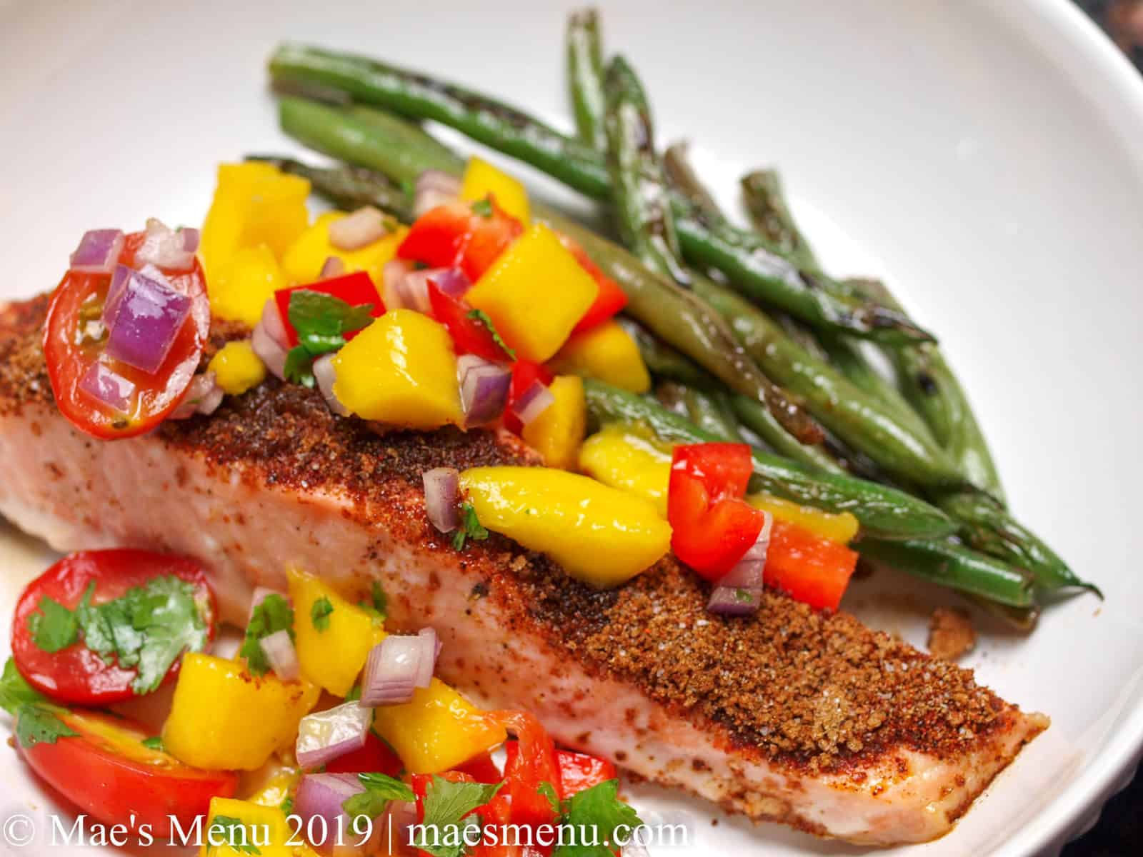 Spicy Baked Salmon with Mango Salsa in a white bowl with green beans