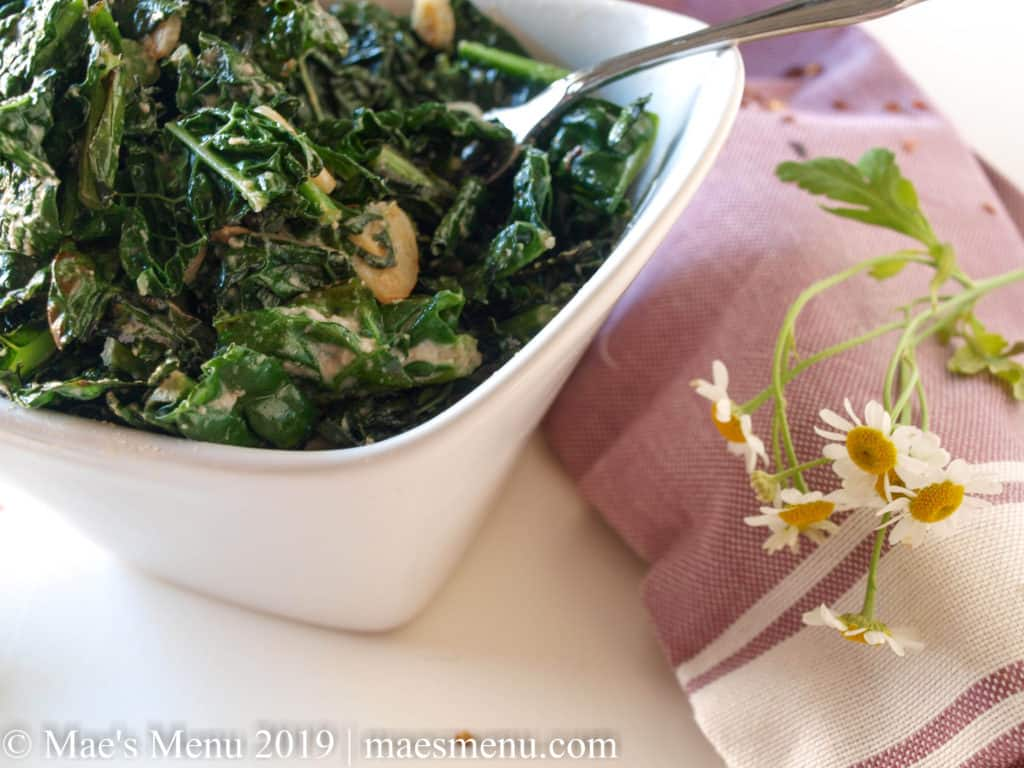 Bowl of warm kale salad and a purple and white dish towel,with white flowers siting on it sit on a white counter.