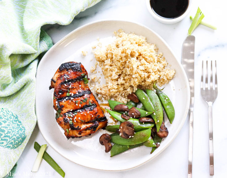 A plate of asian marinated chicken with peas, mushrooms, and quinoa
