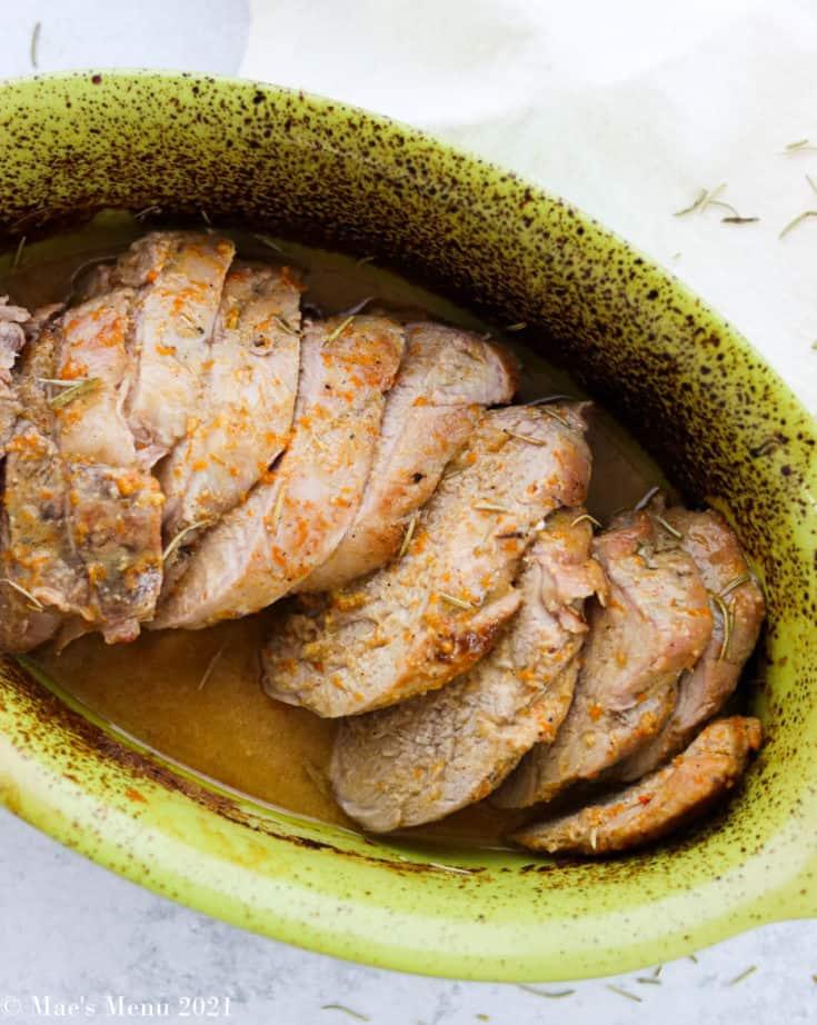 An overhead shot of a green dish of citrus dijon pork tenderloin