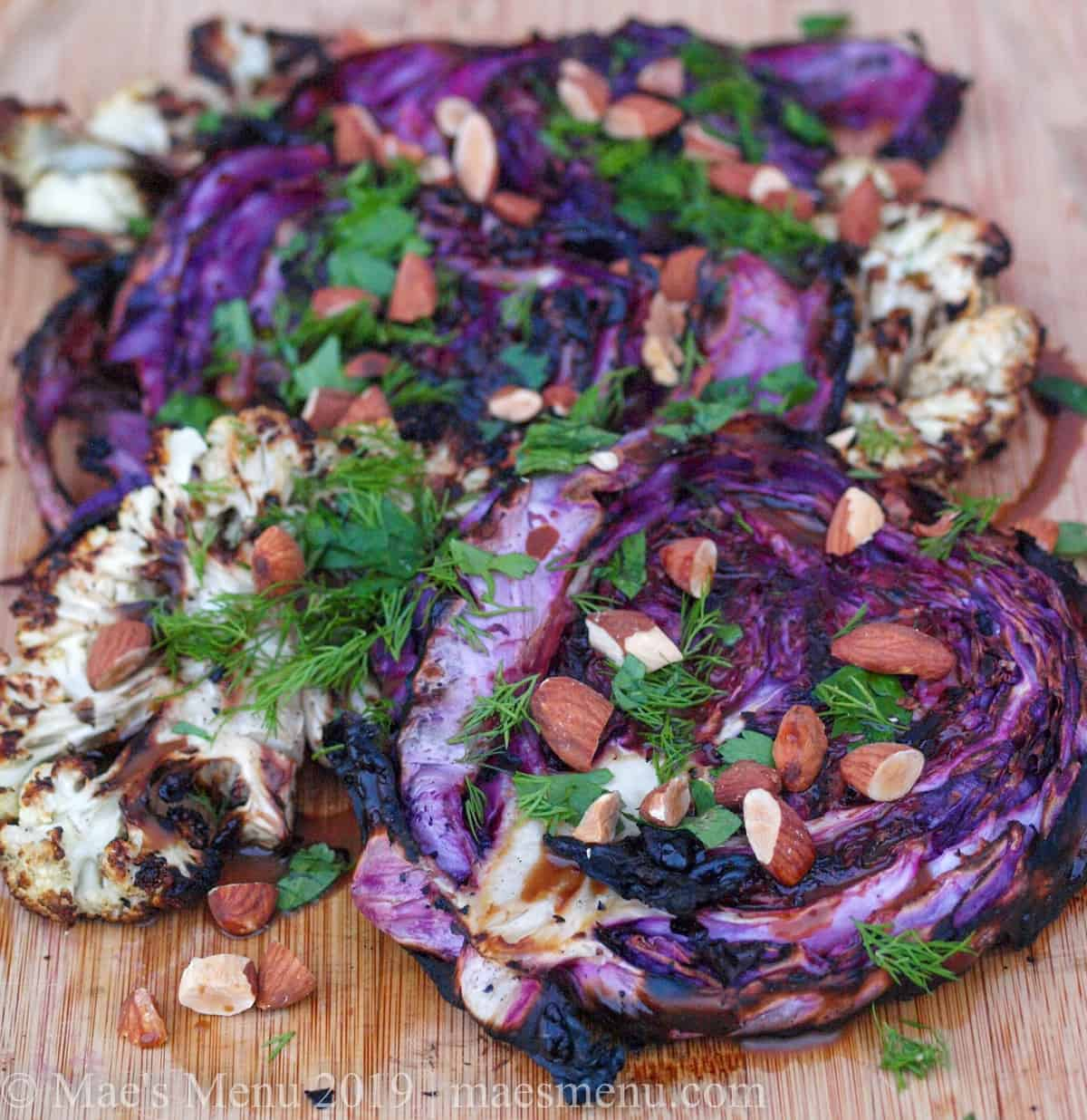 Platter of grilled Cauliflower & Cabbage Salad with miso maple dressing, toasted almonds, and fresh herbs.