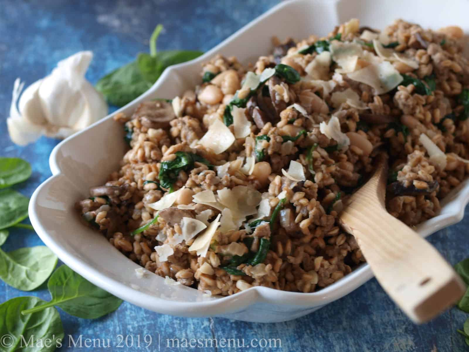 Serving dish of quick mushroom farro risotto next to ahead of garlic and baby spinach leaves.