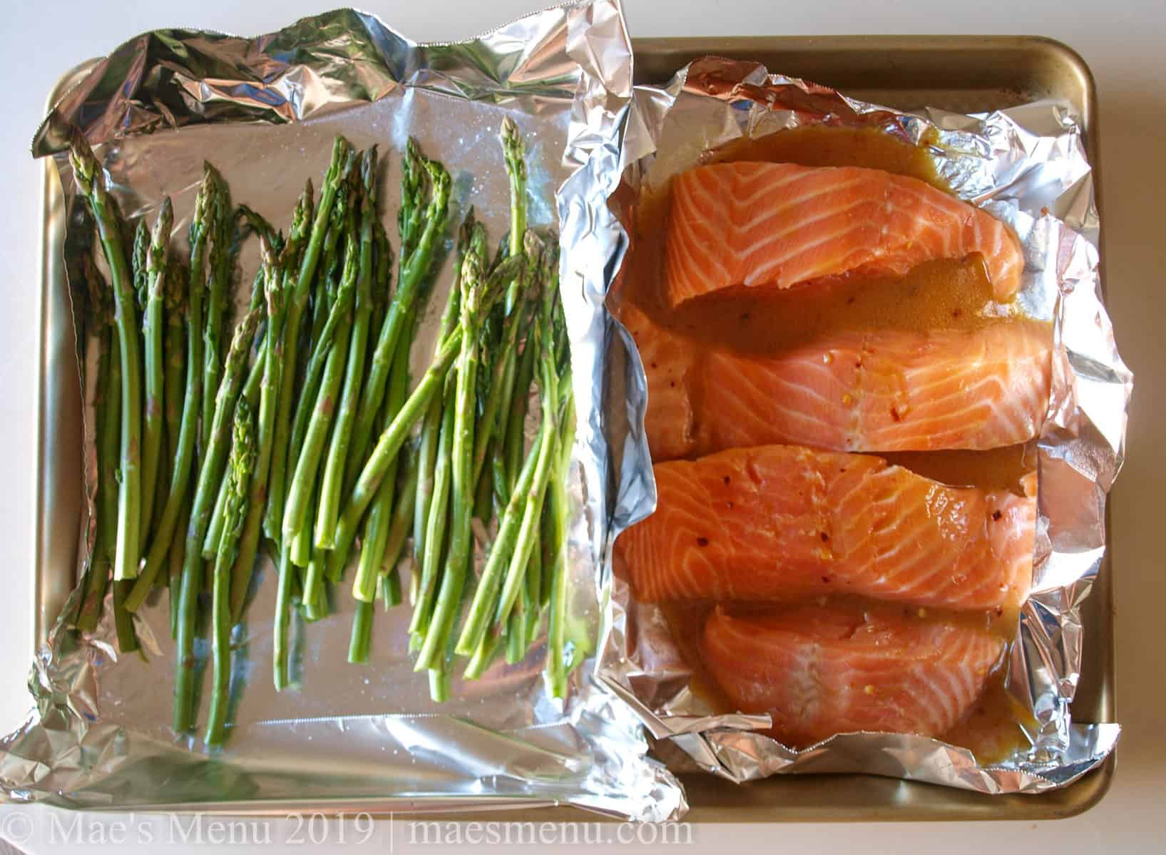 Salmon and asparagus roast in aluminum foil mini trays on a large baking sheet.