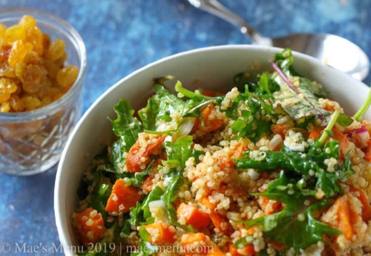 Bowl of Roasted Sweet Potato & Quinoa Salad next to a cup of golden raisins.