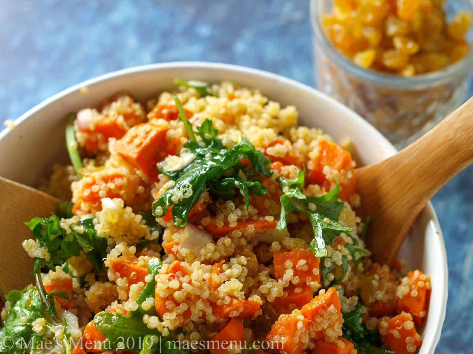 A sweet potato & quinoa salad with a wooden spoon in the bowl