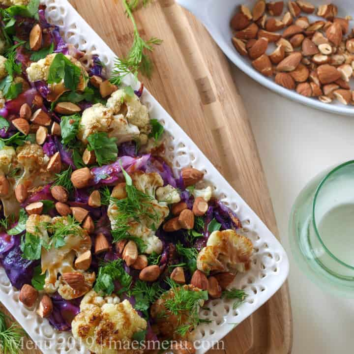 Platter of Roasted Cauliflower & Cabbage Salad Recipe with a glass of sparkling water and dish of roasted nuts.