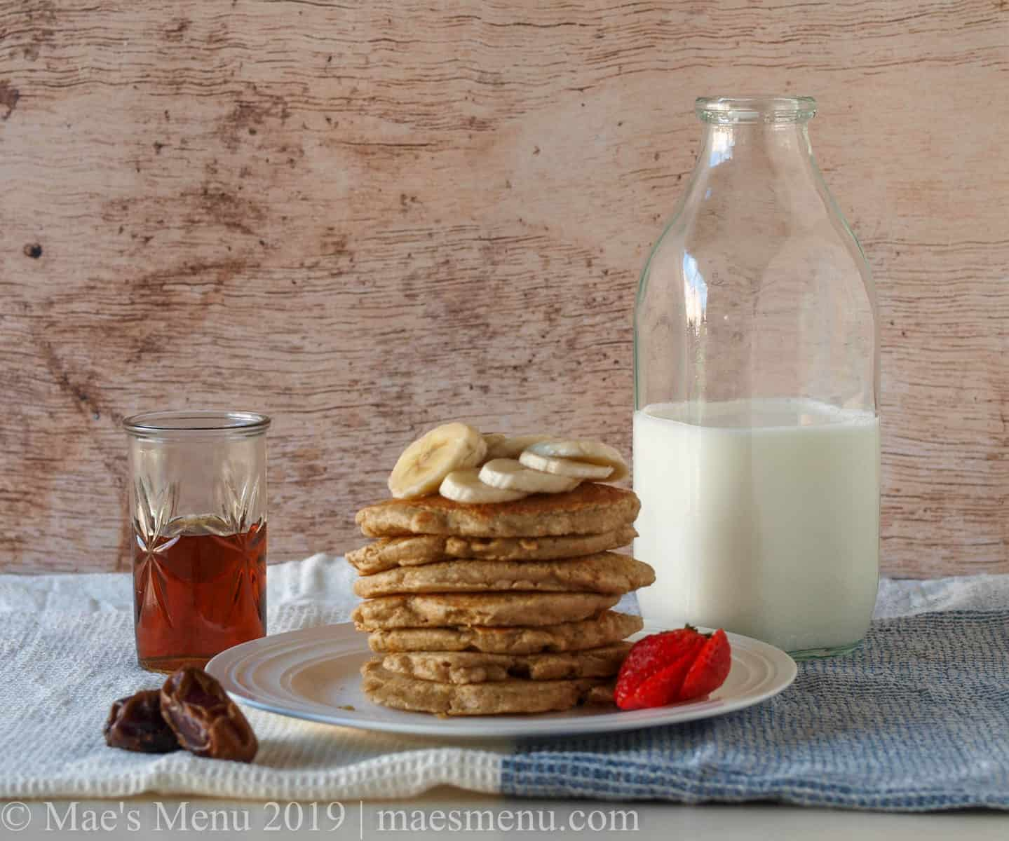 A plate with a stack of oatmeal blender pancakes. On top of the pancakes sits bananas and next to the pancakes sit strawberries. Next to the plate are dates, a cup of maple syrup, and a bottle of milk