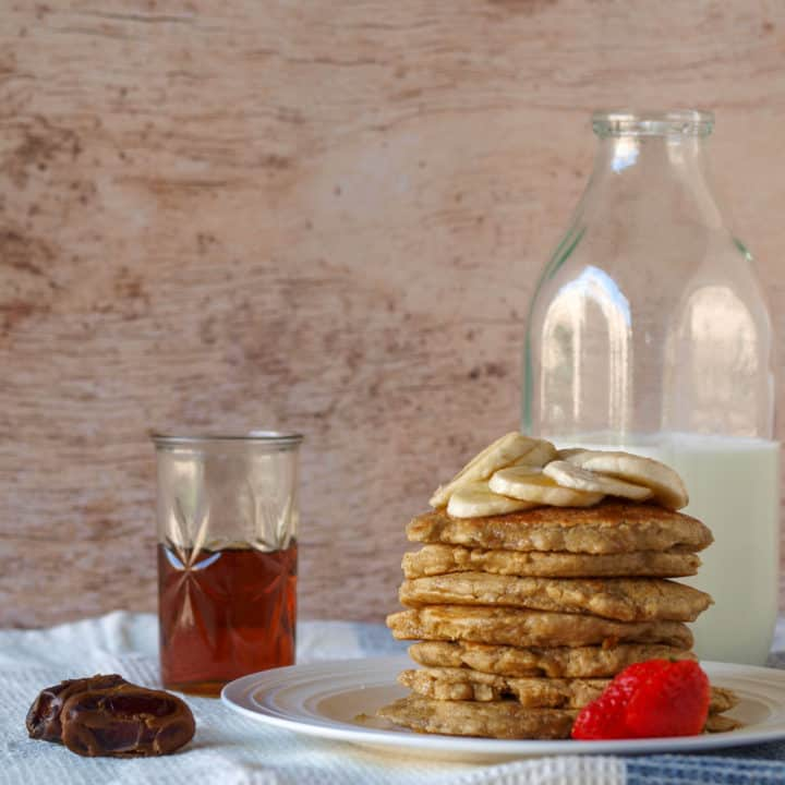 Stack of oatmeal blender pancakes, a bottle of milk, cup of maple syrup, and dates.