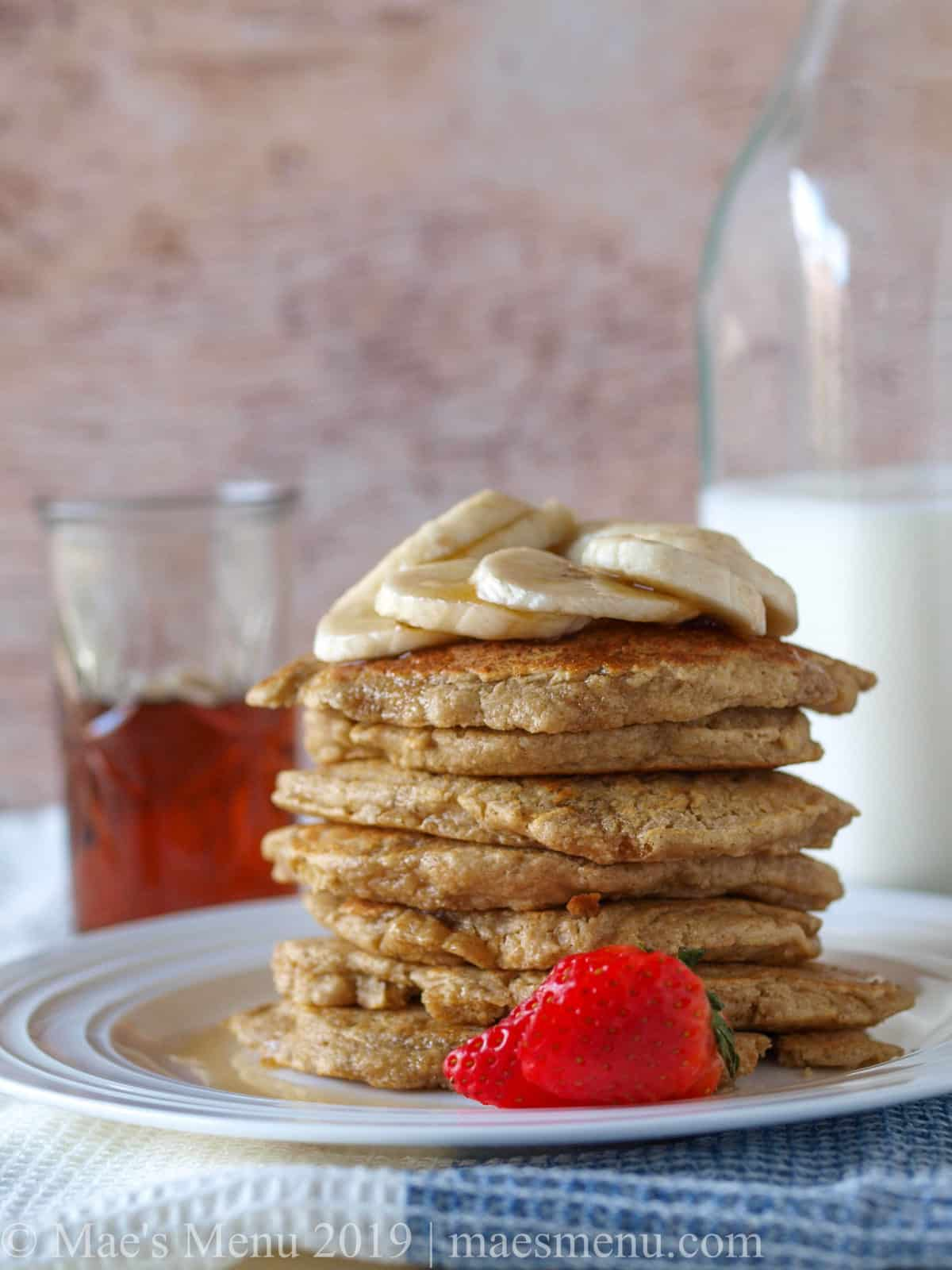 Stack of oatmeal blender pancakes next to bottle of milk and cup of maple syrup