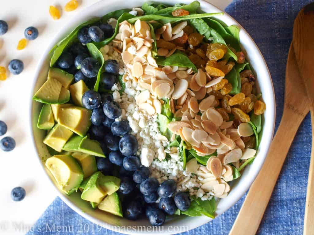A large white bowl of baby spinach, blueberries, avocado, goat cheese, almonds and golden raisins next to salad tongs and a blue towel.