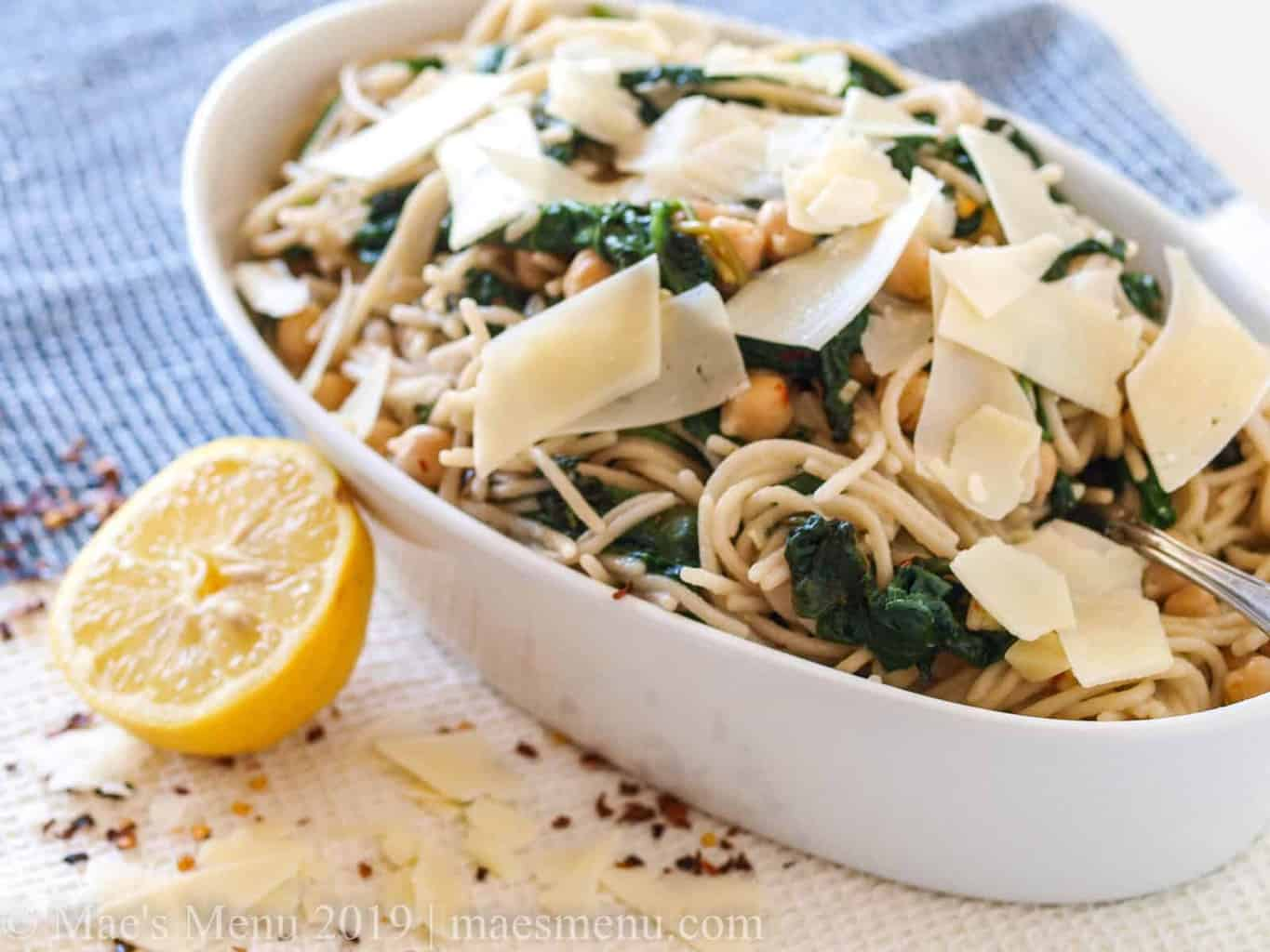 White bowl of spaghetti and garlicky greens.