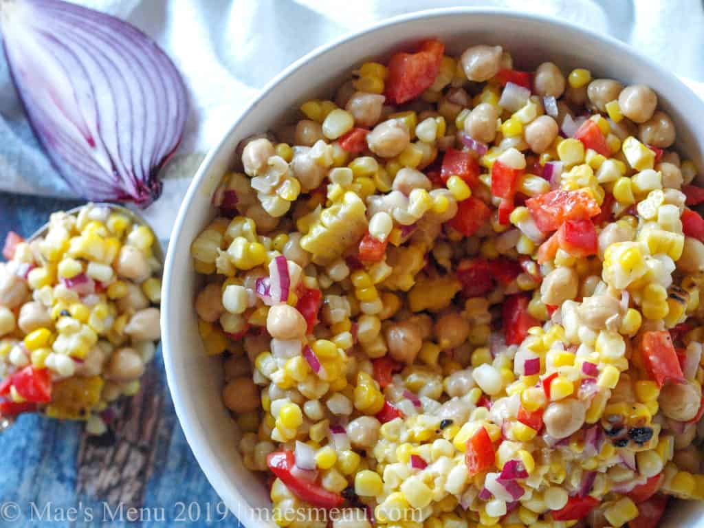 Large white bowl of Chickpea & Grilled Corn Salad with Roasted Garlic Salad Dressing.