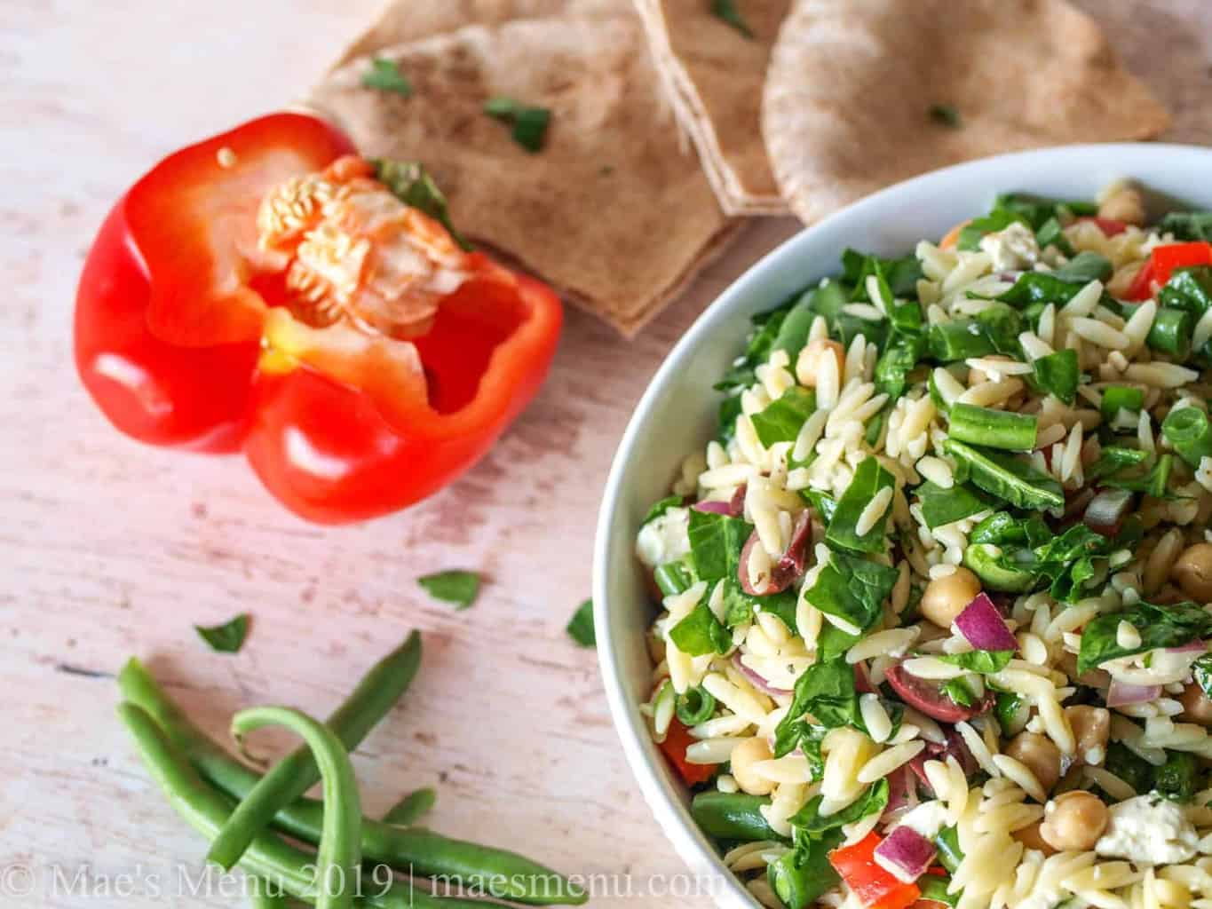 White bowl of Mediterranean Chickpea and Orzo salad next to pita wedges and veggies.