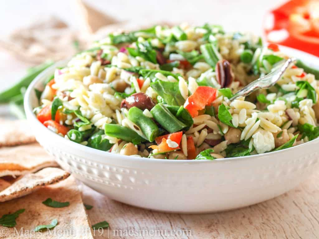 A large bowl of meditteranean chickpea orzo salad next to pita bread, chopped up veggies