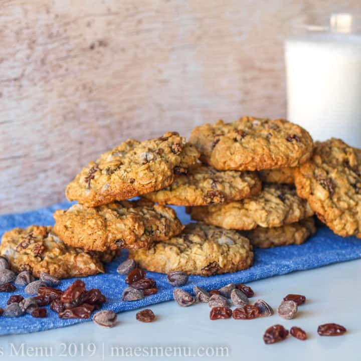 Stack of oatmeal raisin chocolate chip cookies next to a glass of milk.