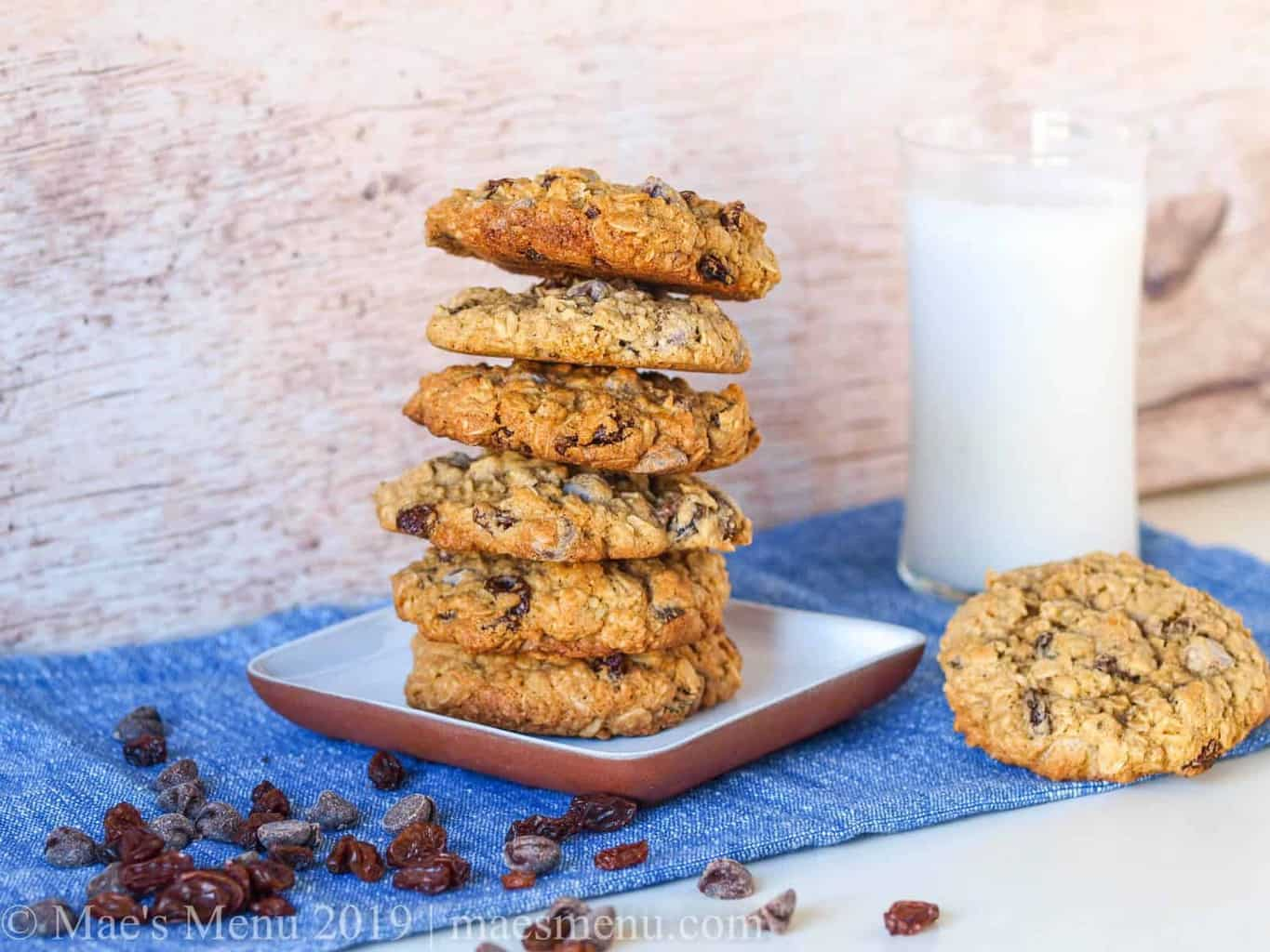 Stack of oatmeal raisin chocolate chip cookies and a glass of milk.