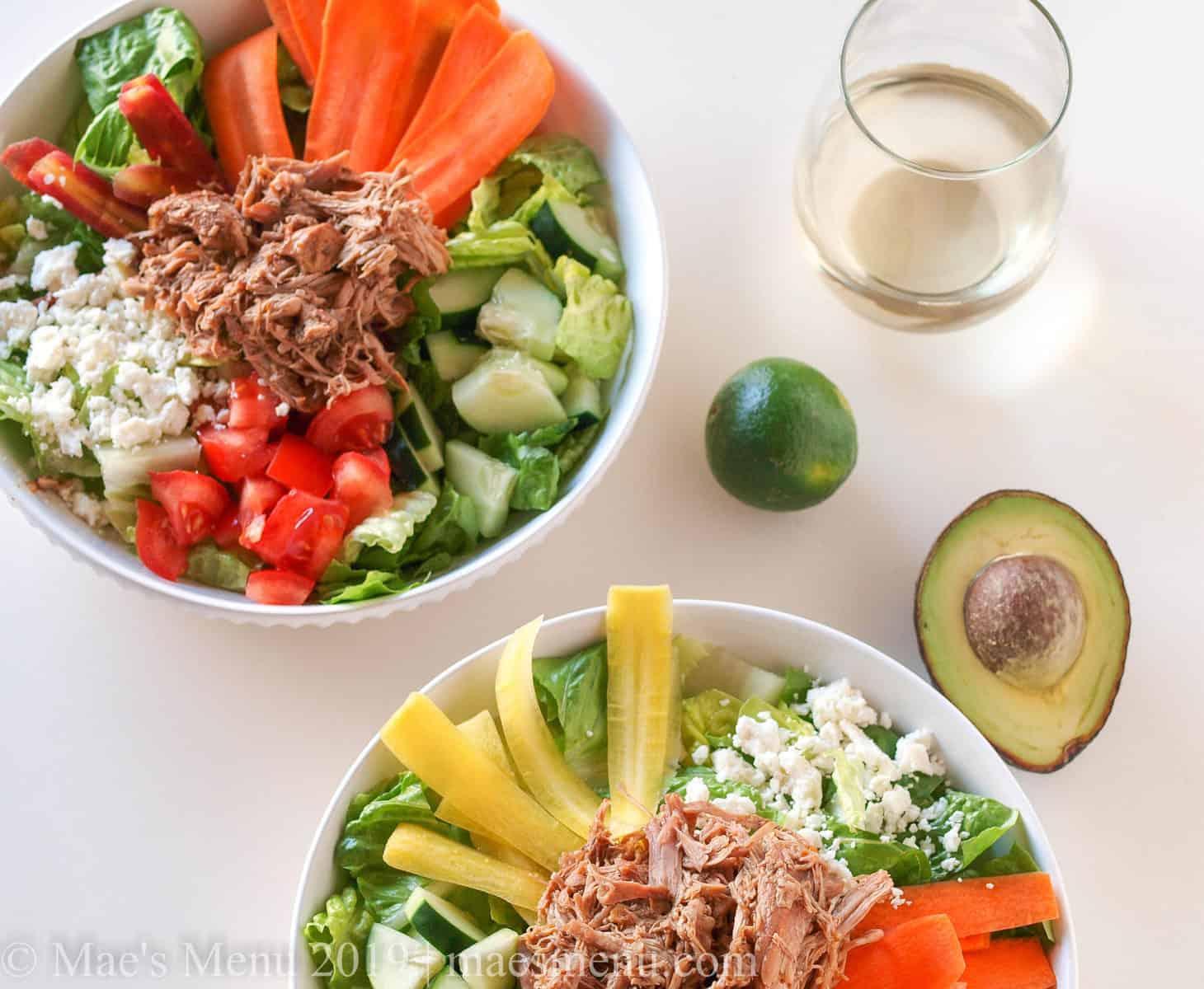 Turkey carnitas bowls next to an avocado, lime, and white wine.
