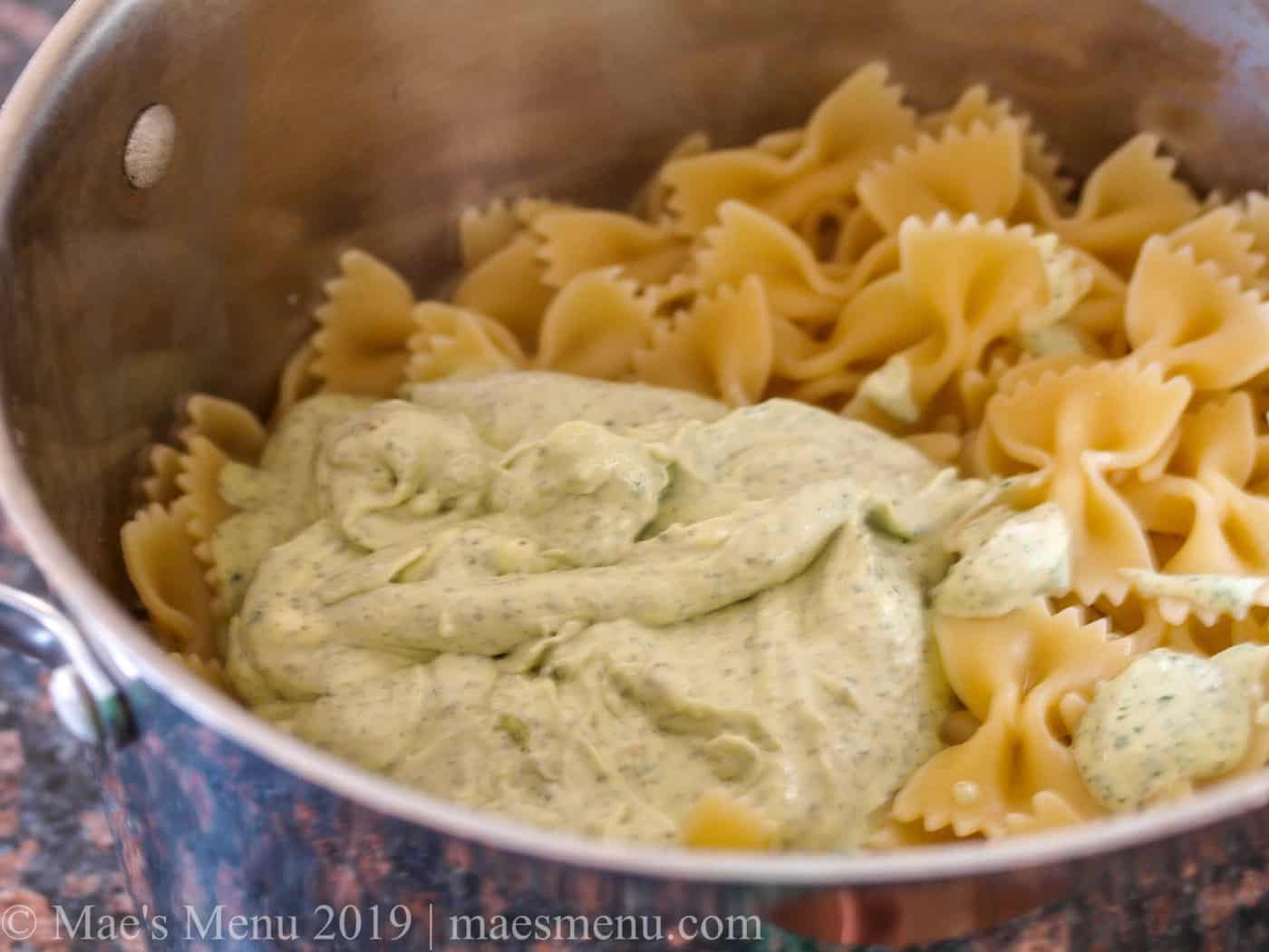 Tossing the creamy chimichurri with the cooked pasta.