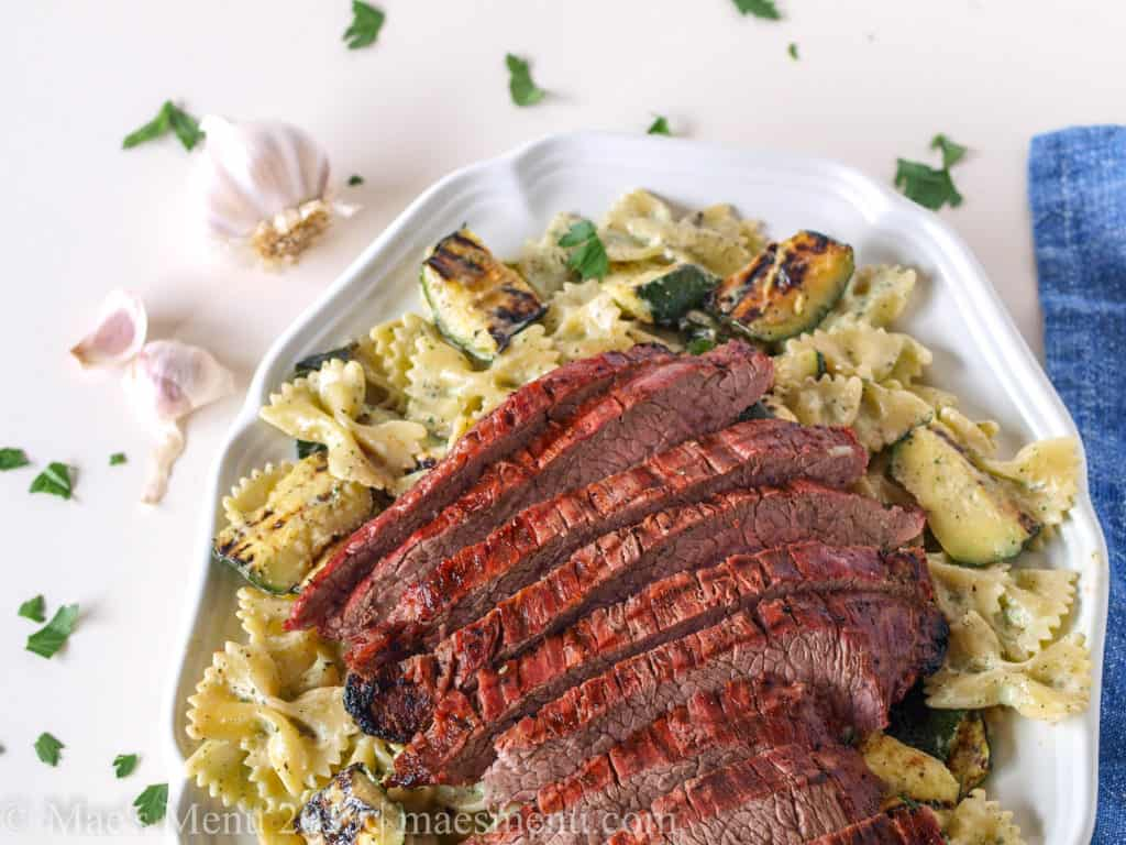 Platte of chimichurry cream pasta with steak.