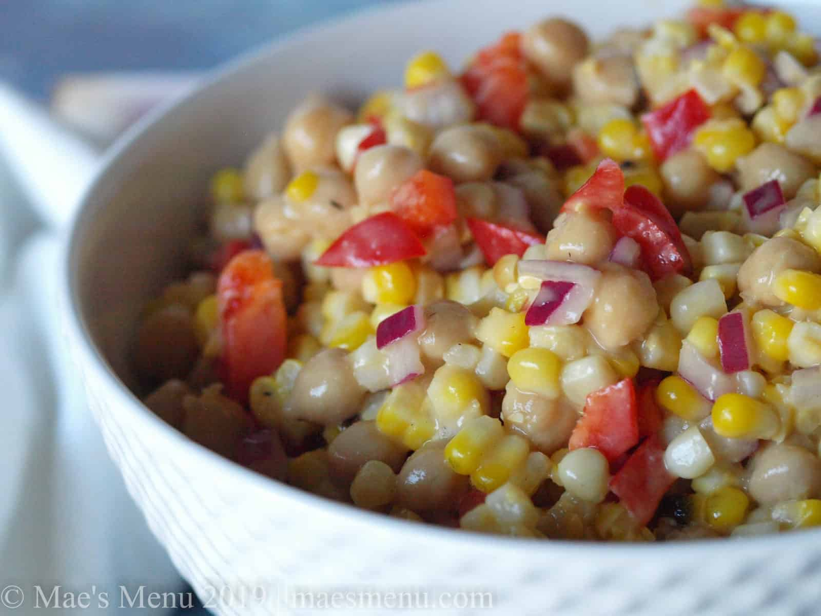 Up-close of chickpea & grilled corn salad with roasted garlic salad dressing.